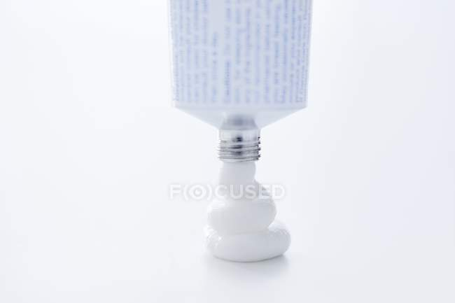 Primer plano de la crema médica blanca que sale del tubo . - foto de stock
