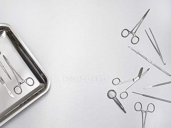 Forbici chirurgiche, utensili e vassoio su sfondo grigio . — Foto stock