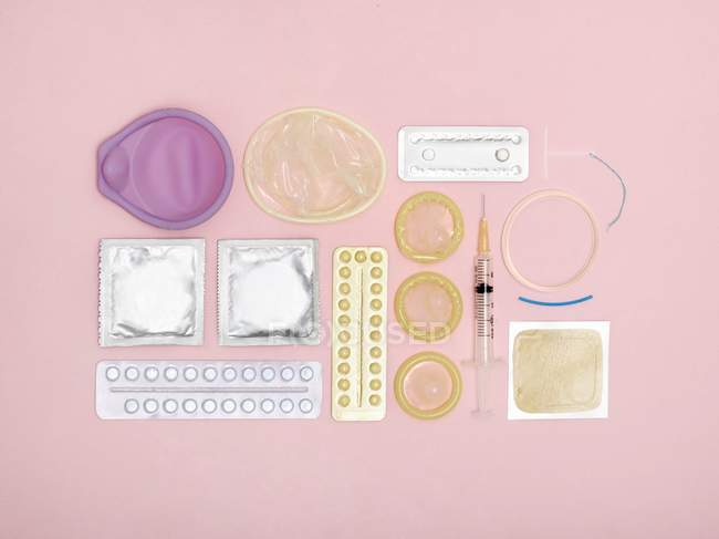 Assortment of contraception techniques against pink background. — Stock Photo