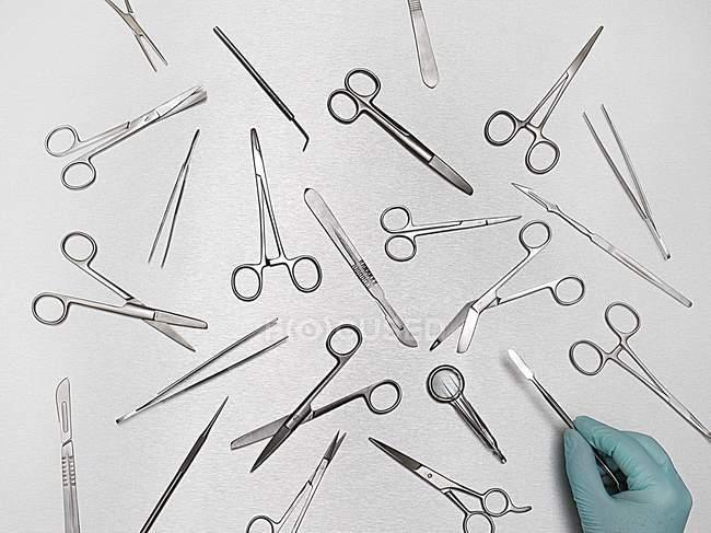 Medico mano selezionando attrezzature chirurgiche su sfondo grigio . — Foto stock
