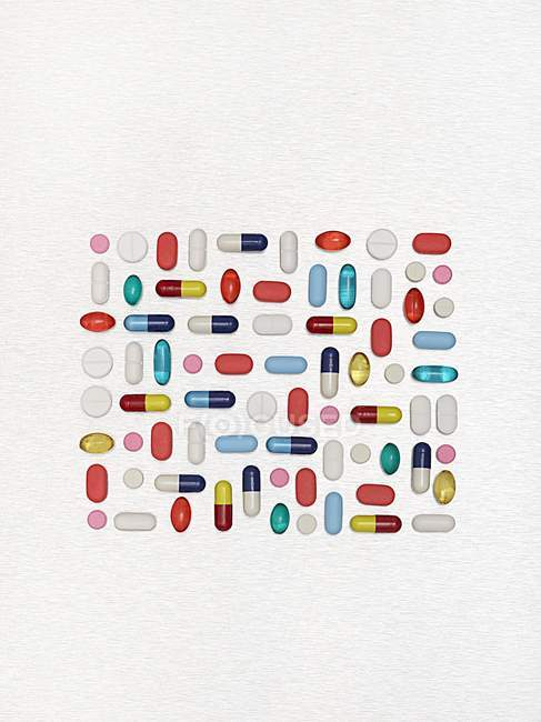 Flat lay of assorted pills and capsules against white background. — Stock Photo