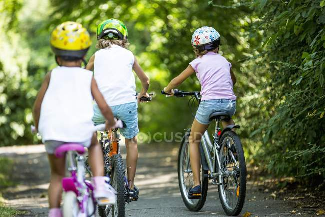 Visão traseira de crianças usando capacetes e ciclismo no parque . — Fotografia de Stock