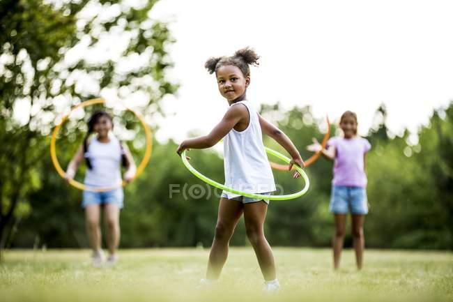Mädchen im Grundschulalter spielen im Sommerpark mit Hula-Hoop-Reifen. — Stockfoto