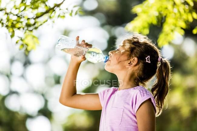 Вид сбоку на девушку, пьющую воду из пластиковой бутылки в парке . — стоковое фото
