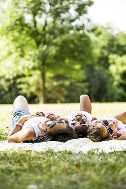 Mädchen mit Sonnenbrille liegen Seite an Seite auf Decke im Park. — Stockfoto