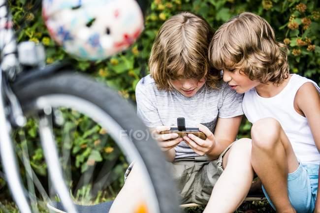 Niños jugando juego en el teléfono inteligente detrás de la bicicleta en el parque . - foto de stock