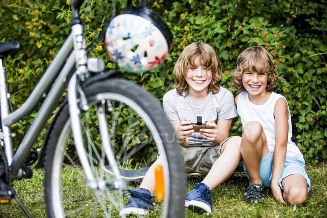 Meninos sentados com telefone celular de bicicleta com capacete . — Fotografia de Stock