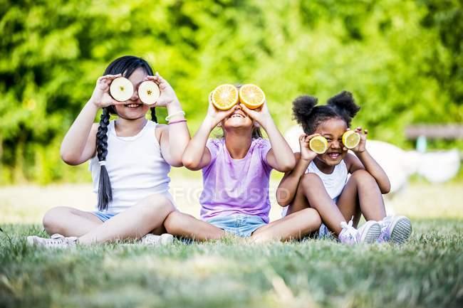 Mädchen im Grundschulalter sitzen Seite an Seite im Park und bedecken die Augen mit Fruchtscheiben. — Stockfoto