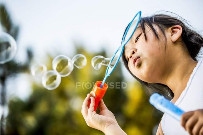 Девчонка-азиатка с низким углом обдувает пузыри палочкой в парке . — стоковое фото