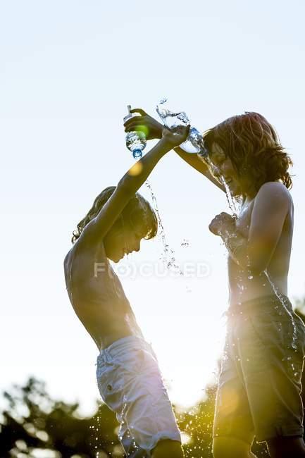 Ragazzi versando acqua l'uno sull'altro da bottiglia di plastica e ridendo . — Foto stock
