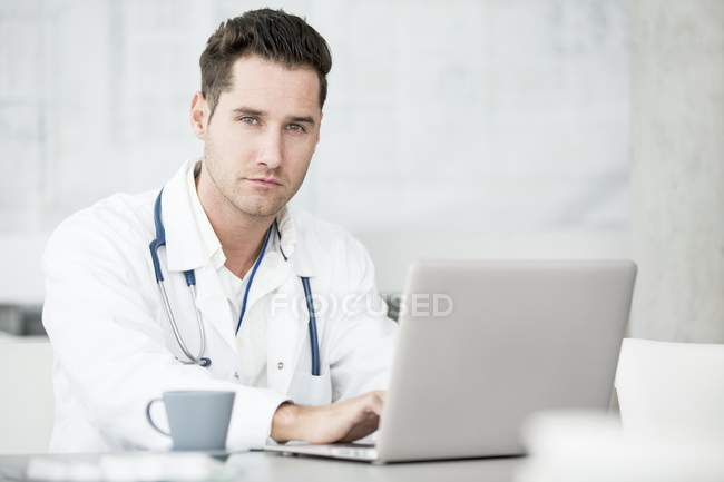 Médico masculino adulto médio usando laptop na mesa com copo . — Fotografia de Stock