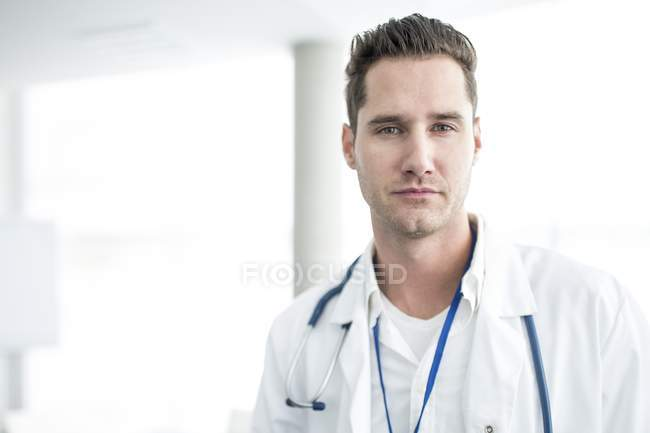 Portrait of mid adult male doctor looking in camera. — Stock Photo