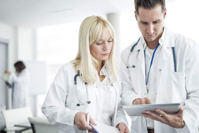 Male and female doctors inspecting digital tablet. — Stock Photo