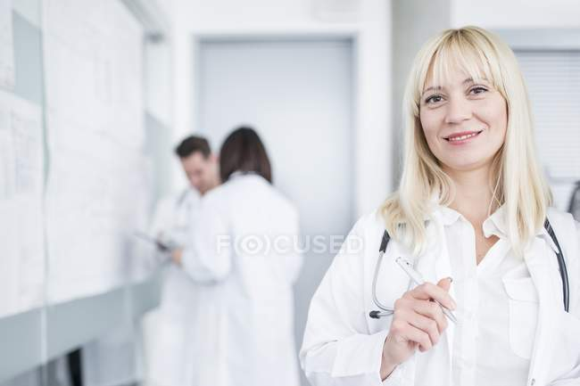 Portrait of female doctor smiling in camera with colleagues in background. — Stock Photo