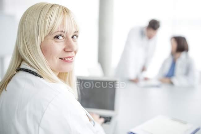Médecin féminin regardant par-dessus l'épaule et souriant à l'intérieur de la clinique . — Photo de stock