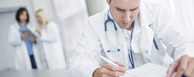Mid adult male doctor doing paperwork with colleagues in background. — Stock Photo