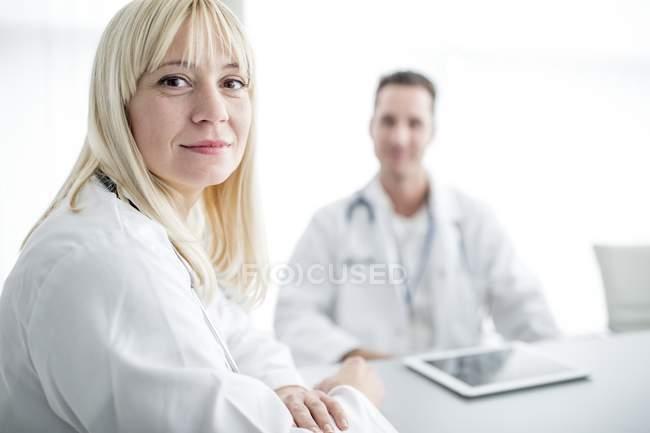 Médica feminina olhando por cima do ombro e sorrindo no interior da clínica . — Fotografia de Stock