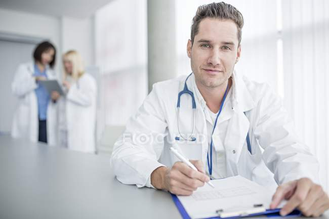Mid adult male doctor doing paperwork and looking in camera. — Stock Photo