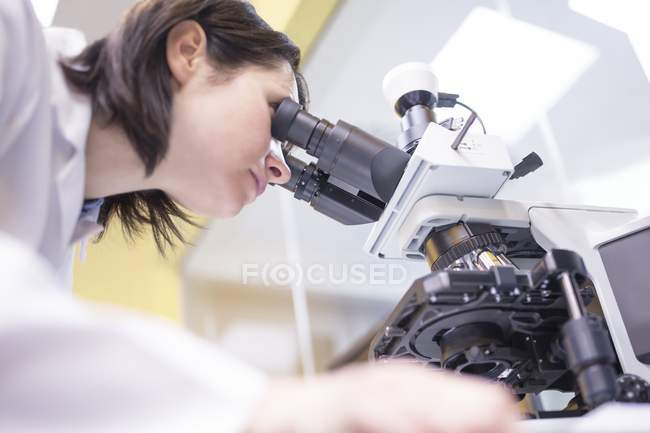 Female laboratory technician using microscope in laboratory. — Stock Photo