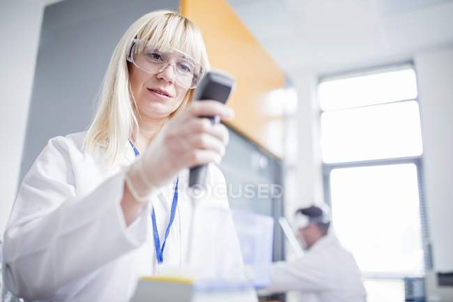Femme scientifique portant des lunettes de protection et utilisant un dispositif . — Photo de stock