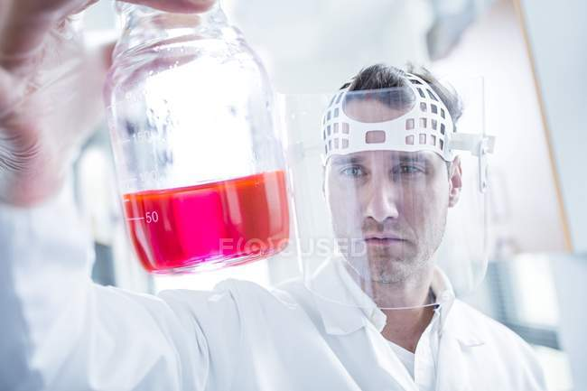 Male scientist wearing protective mask and holding flask with pink liquid. — Stock Photo