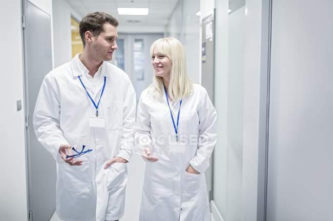 Médicos masculinos e femininos em casacos brancos corredor. — Fotografia de Stock