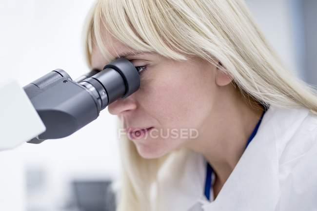 Female laboratory technician using microscope in lab. — Stock Photo