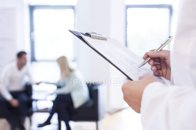 Hands of doctor making notes with patients talking in background. — Stock Photo
