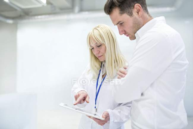 Female doctor discussing medical notes on digital tablet with consultant. — Stock Photo