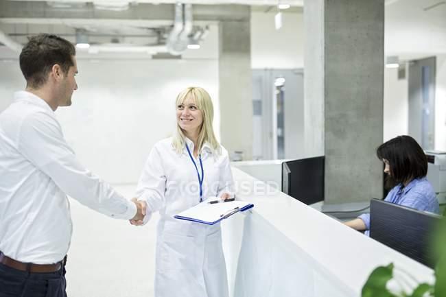 Женщина-врач Пожатие руки мужчины пациента в больницу стол. — стоковое фото