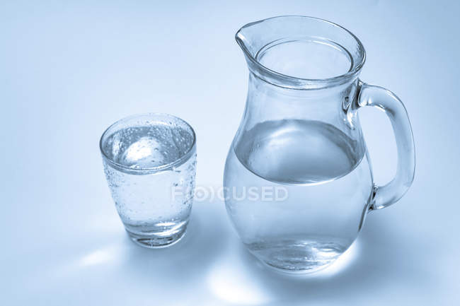 Glass and jug of mineral water on plain background. — Stock Photo