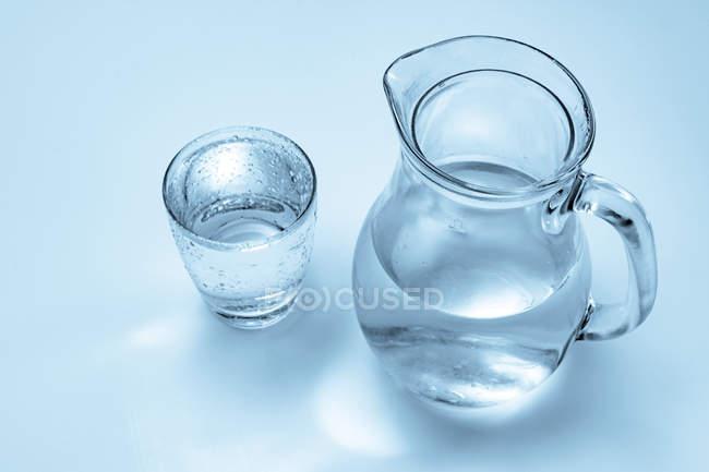 Скло і глечик мінеральної води на просте тло. — стокове фото