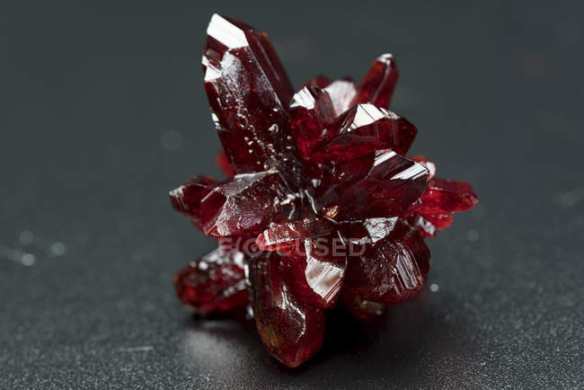 Red crystal mineral stone on table, close-up. — Stock Photo