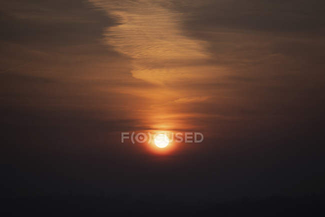 Scenic cloudscape on dark sky with glowing sun at sunset. — Stock Photo