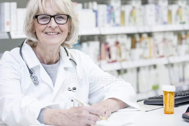 Portrait of smiling senior pharmacist writing on prescription. — Stock Photo