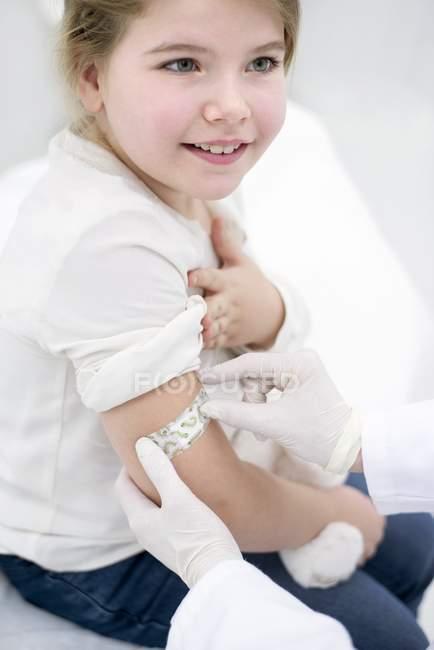 Doutor colando gesso no braço da menina após a injeção na clínica médica . — Fotografia de Stock