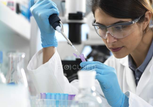 Scientist pipetting sample into tube for analytical testing in laboratory. — Stock Photo