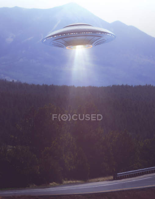 Composite image of unidentified flying object illuminating road. — Stock Photo