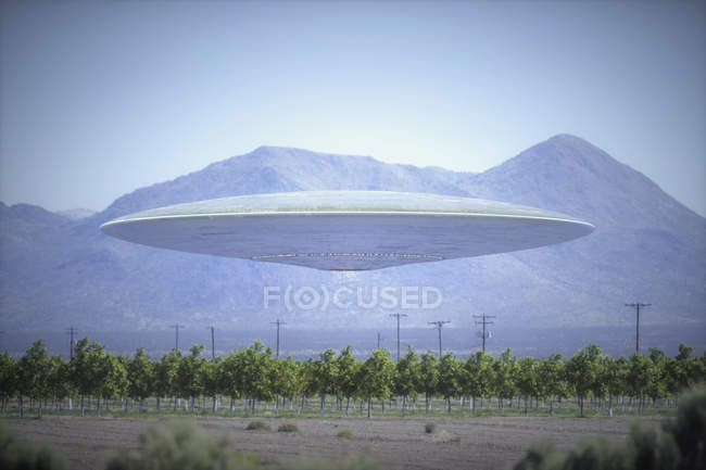 Composite image of unidentified flying object flying over plantation with mountains behind. — Stock Photo