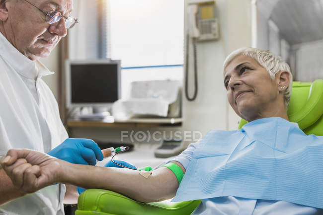Senior doctor drawing female patient blood for PRP cosmetics treatment. — Stock Photo