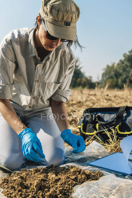 Female agronomist taking soil fertility analysis sample. — Stock Photo