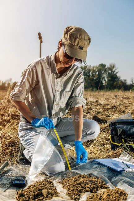 Agronomist opening soil sample bag in field. — Stock Photo