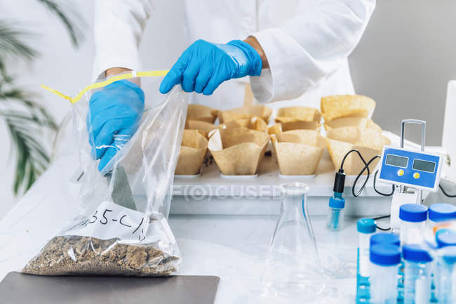 Biologist pouring soil with spatula from sample bag into separated containers. — Stock Photo