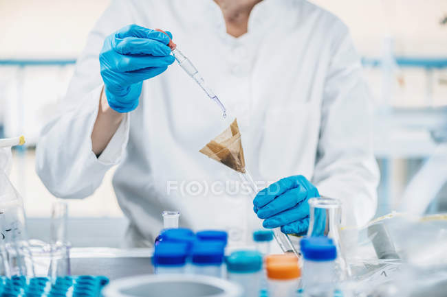 Mid section of scientist in laboratory mixing samples of soil with reagent. — Stock Photo