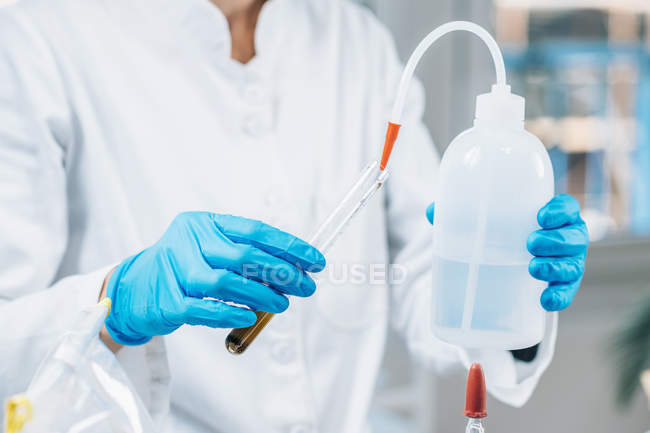 Female biologist in white coat pouring water into test tube with dissolved samples of soil in laboratory. — Stock Photo