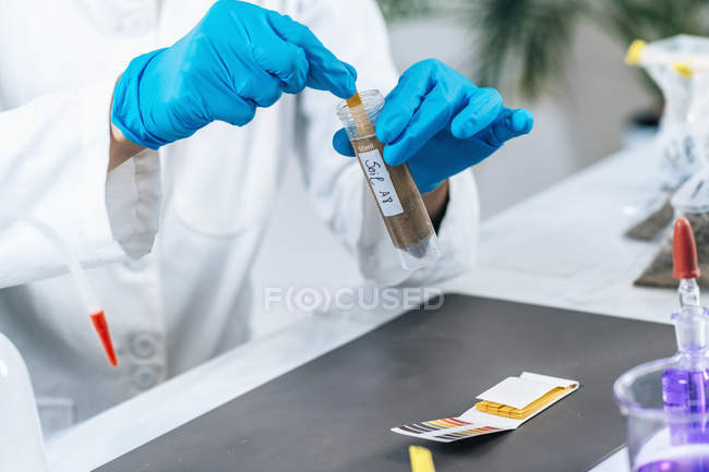 Female scientist in white coat measuring PH of soil sample with litmus strips. — Stock Photo