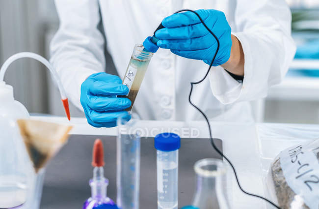 Hands of scientist in laboratory measuring pH of soil samples by electronic pH meter. — Stock Photo