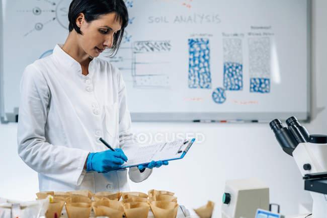 Female scientist in white coat taking notes in soil testing laboratory. — Stock Photo