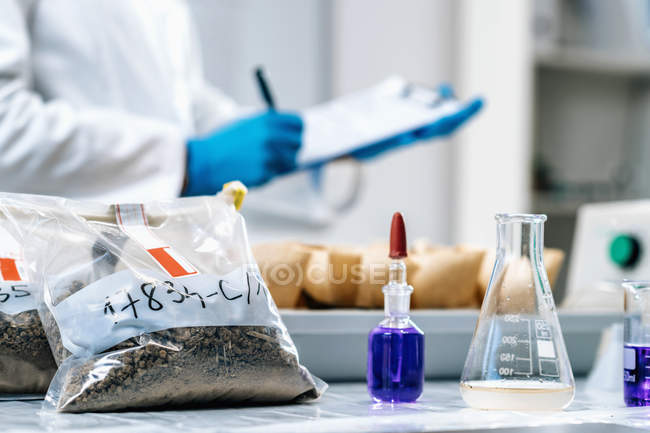 Primer plano de la científica tomando notas en el laboratorio de pruebas de suelo . - foto de stock