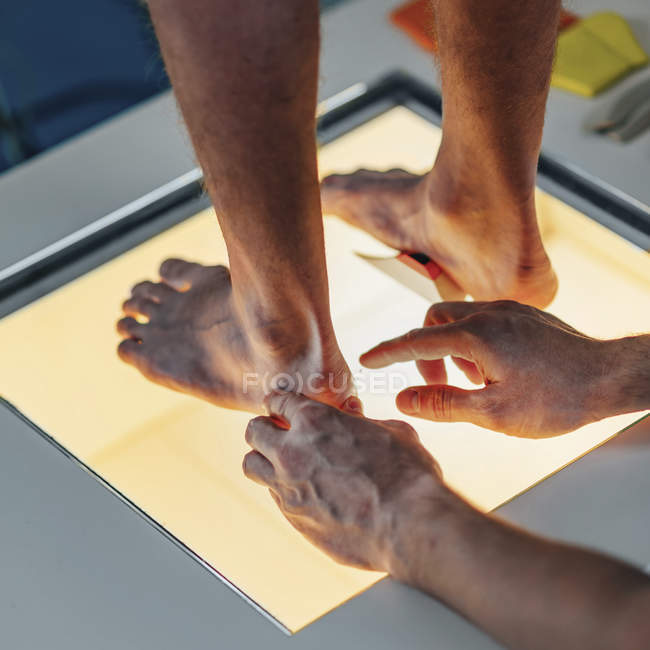Physical therapist performing foot pressure scan for child on illuminated platform. - foto de stock